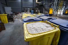 Containers with shredded plastic prepared for further processing remelting and recycling with shredder and bales of plastic waste royalty free stock images