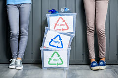 Containers with sorted waste. Three containers with glass, paper and plastic waste indoors with female legs on the wall background royalty free stock photo
