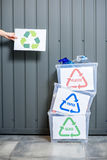 Containers with sorted waste. Three containers with glass, paper and plastic waste indoors on the wall background royalty free stock photography