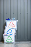Containers with sorted waste. Three containers with glass, paper and plastic waste indoors on the wall background stock images