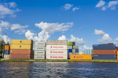 Containers from Yangming, Hapag-Loyd, MSC, NYK, Triton, Gold are placed along the shore. Royalty Free Stock Image