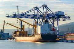 Containerschiff lädt in einem Hafen und glättet Licht stockfotografie