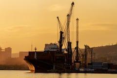 Containerschiff lädt in einem Hafen und glättet Licht lizenzfreie stockbilder