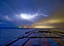 Containerschiff in Meer mit Blitz im Himmel Stockbild