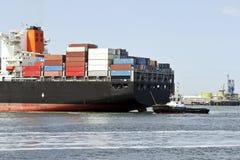 Containerschiff mit Versuchsboot Stockfotos