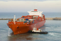 Containerschiff und ein kleines Schlepperboot Lizenzfreies Stockbild