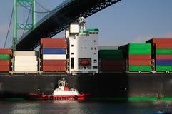 Containerschiff und roter Schlepper stockfotografie