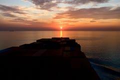 Containerschiff und Sonnenuntergang Stockfotografie