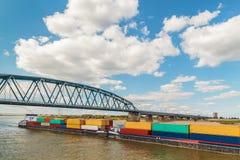 Containerschip die een brug op de Nederlandse rivier Waal in Nij overgaan stock afbeeldingen