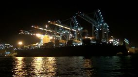 Nocturne footage in Algeciras cargo with containership downloading. Containership of loading and downloading cargo in Algeciras harbor terminal in Algeciras bay stock video footage
