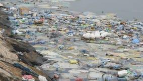 Contaminación ambiental Botellas plásticas, bolsos, basura en el río, lago Desperdicios y contaminación que flotan en agua almacen de metraje de vídeo