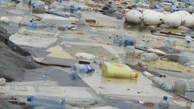 Contaminación ambiental Botellas plásticas, bolsos, basura en el río, lago Desperdicios y contaminación que flotan en agua metrajes