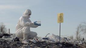 Contaminación ambiental, científico de la mujer en los guantes uniformes y protectores que sostienen los tubos de ensayo y que re almacen de metraje de vídeo