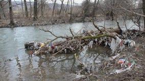 Contaminación ambiental Las bolsas de plástico, botellas, basura y basura flotando en el río contaminado Desperdicios y basura en almacen de video