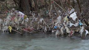 Contaminación ambiental Las bolsas de plástico, botellas, basura y basura flotando en el río contaminado Desperdicios y basura en almacen de metraje de vídeo