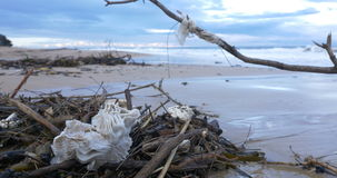 Contaminación plástica de las aguas residuales de la basura en la playa por el mar del océano almacen de metraje de vídeo