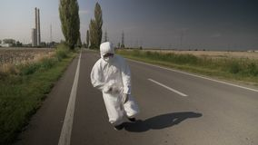 Contaminated ecologist worker in hazmat suit chocking and falling down on drive way near refinery and dying -. Contaminated ecologist worker in hazmat suit stock footage