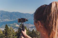 Contaminazione della ragazza con il giunto cardanico nelle montagne sopra il maggiore del lago immagini stock libere da diritti