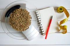 Contando calorias, gordura, hidratos de carbono e proteínas no alimento Sementes da lentilha em escalas da cozinha foto de stock