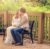 Contando con la mamá y al papá que se besan en patio bench al aire libre Imagenes de archivo