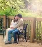 Contando con la mamá y al papá que se sientan en patio bench al aire libre Imagen de archivo