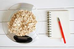 Contando e gravando a quantidade de calorias, de proteínas, de hidratos de carbono e de gorduras no alimento Flocos de quatro cer imagem de stock