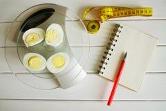 Contando a quantidade de proteína, de gordura, de hidratos de carbono e de calorias no alimento Ovo da galinha nas escalas da coz fotografia de stock royalty free