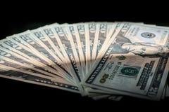 Contant geld op een zwarte achtergrond uit wordt gewaaid die Stock Foto