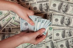 Contant geld ter beschikking Winst, besparingen Stapel dollars een persoon die geld tegen de achtergrond van geld, succes, motiva stock afbeelding