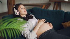 Contar con a la madre es relajante en el sofá, escuchando la música con los auriculares y la caricia de su panza con amor y cuida almacen de video