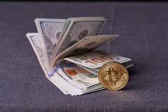 Contas belamente arranjadas 100 bitcoin da moeda do dólar e de ouro em um fundo cinzento Cryptocurrency de Bitcoin anonymous Fund fotos de stock