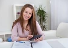 Contas calculadoras da jovem mulher Foto de Stock Royalty Free