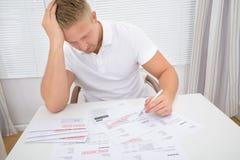 Contas calculadoras preocupadas do homem Imagens de Stock Royalty Free