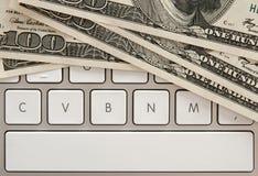 Contas de dinheiro no teclado de computador com barra espaçadora Fotografia de Stock Royalty Free