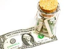 contas de Um-dólar em um frasco de vidro, em um fundo branco Fotos de Stock