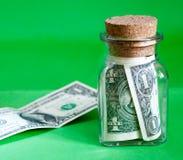 contas de Um-dólar em um frasco de vidro, em um fundo verde Fotografia de Stock