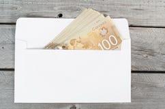 Contas do canadense 100 no envelope branco Imagem de Stock Royalty Free