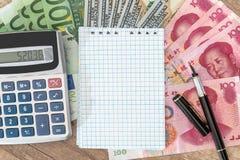 100 contas do dólar, do euro e do yuan com bloco de notas e calculadora e pena Foto de Stock