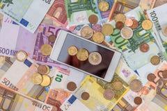 Contas do Euro com moeda, smartphone Imagem de Stock