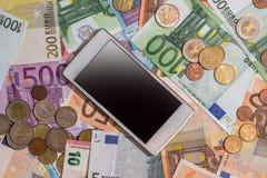 Contas do Euro com moeda, smartphone Fotos de Stock Royalty Free