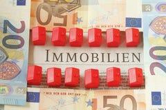 Contas do Euro, dinheiro, casas pequenas vermelhas dos brinquedos Fotografia de Stock