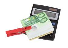 Contas do Euro mantidas unidas por um pregador de roupa vermelho com calculadora Fotos de Stock Royalty Free