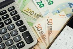 Contas e calculadora de dinheiro do Euro Foto de Stock