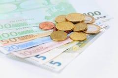 Contas e moedas do Euro com um fundo branco Imagens de Stock