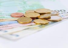 Contas e moedas do Euro em um fundo branco Fotografia de Stock Royalty Free
