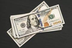 Contas novas de cem-dólar dos E.U. em uma tabela textured de madeira preta Vista de acima Conceitos do dinheiro e da finança 100 Imagem de Stock Royalty Free