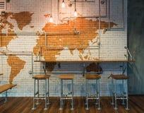 Contatore Antivari della Tabella con la lampadina e delle sedie sopra il muro di mattoni Immagine Stock