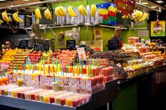 Contatore con i frullati saporiti della frutta, varietà di frutti al mercato di Boqueria a Barcellona Juice For Sale In naturale  fotografia stock libera da diritti