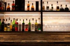 Contatore di legno scuro vuoto della barra con le bottiglie del fondo della sfuocatura fotografia stock libera da diritti