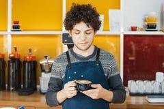 Contatore vicino della barra della tazza di caffè della tenuta di barista in caffè moderno luminoso fotografia stock libera da diritti